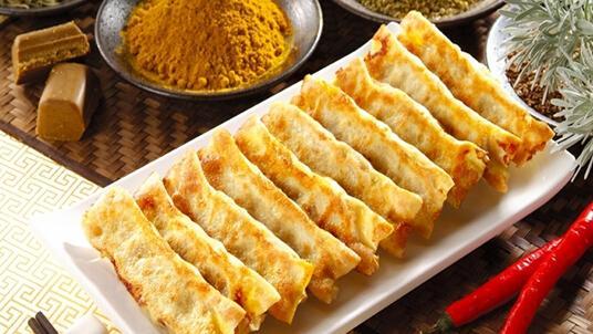 外皮金黄口感酥脆,形状像月牙的的大众小吃,锅贴