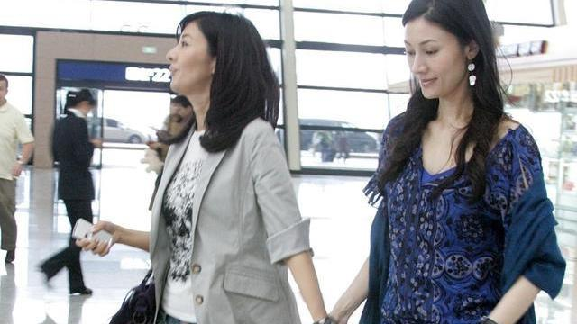 李嘉欣罕见和亲姐走机场,姐姐一看就精明人,脖子上的大包更抢镜