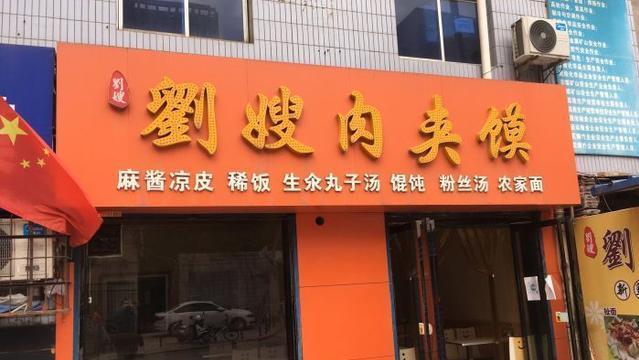 西安大嫂街头卖肉夹馍,饼是现打的,食客蹲在路边吃得欢