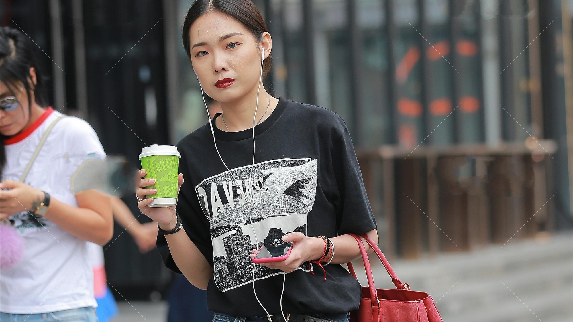 黑色T恤圆领短袖设计,宽松版型搭配红色手提包,随性休闲的穿搭