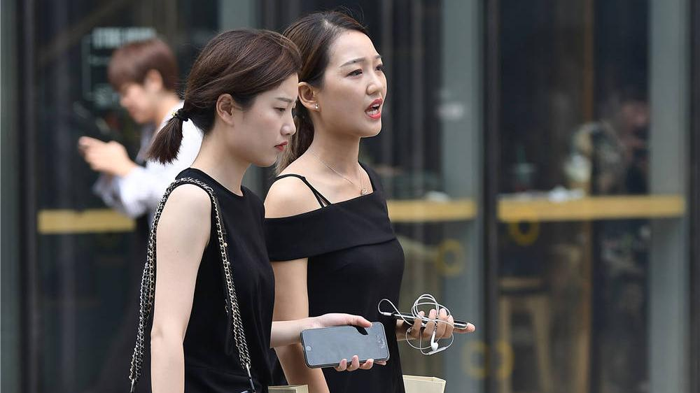 闺蜜穿着款式相似的细跟凉鞋,不同款式的黑色连衣裙,味道不同