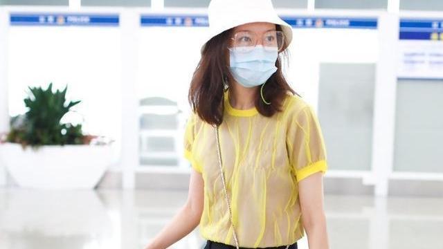 高露真机场穿搭真洋气,黄色T恤配黑色短裤青春靓丽,活力十足