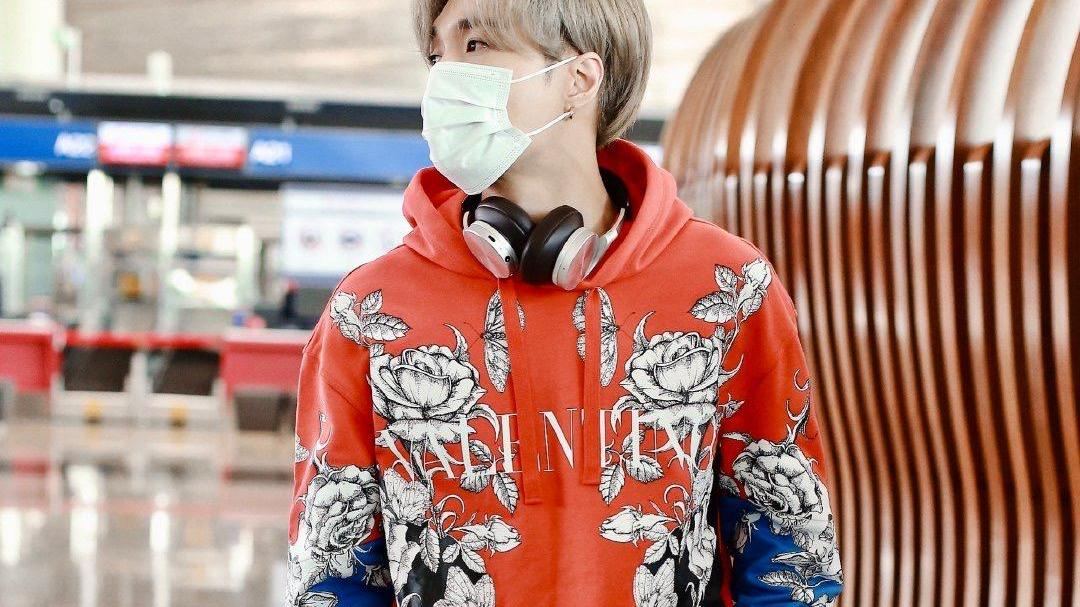 张艺兴新发色现身机场,红色印花卫衣配短裤,耳机挂在脖子上好潮