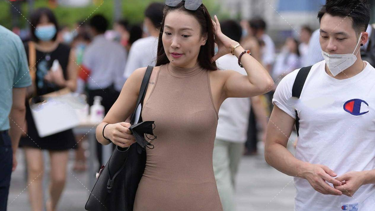 身穿深咖色针织套头连衣长裙,漫步街头,优雅自信