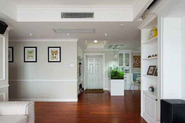 客廳望去玄關處,紅色木地板磚,搭配白色墻面,空間很溫馨明朗.