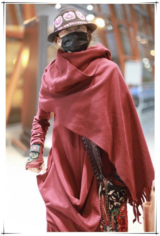 杨丽萍不赶时髦不扮嫩,穿大红袍踩花盆鞋走机场,60岁也惊艳