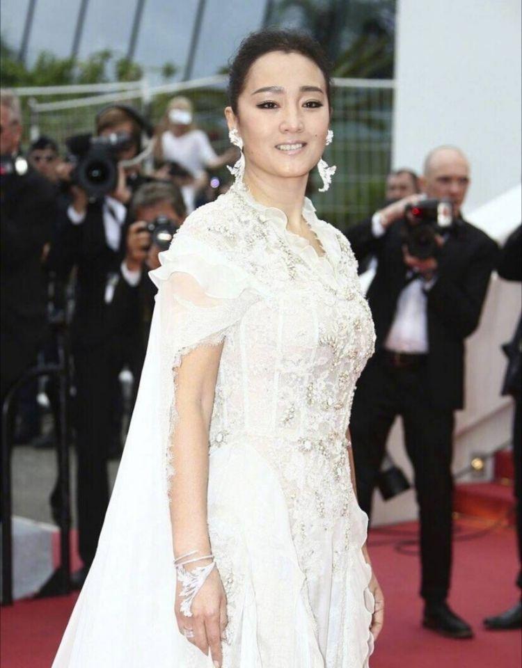 巩俐第18次亮相戛纳红毯,白色披风纱裙仙气十足,女王驾到!