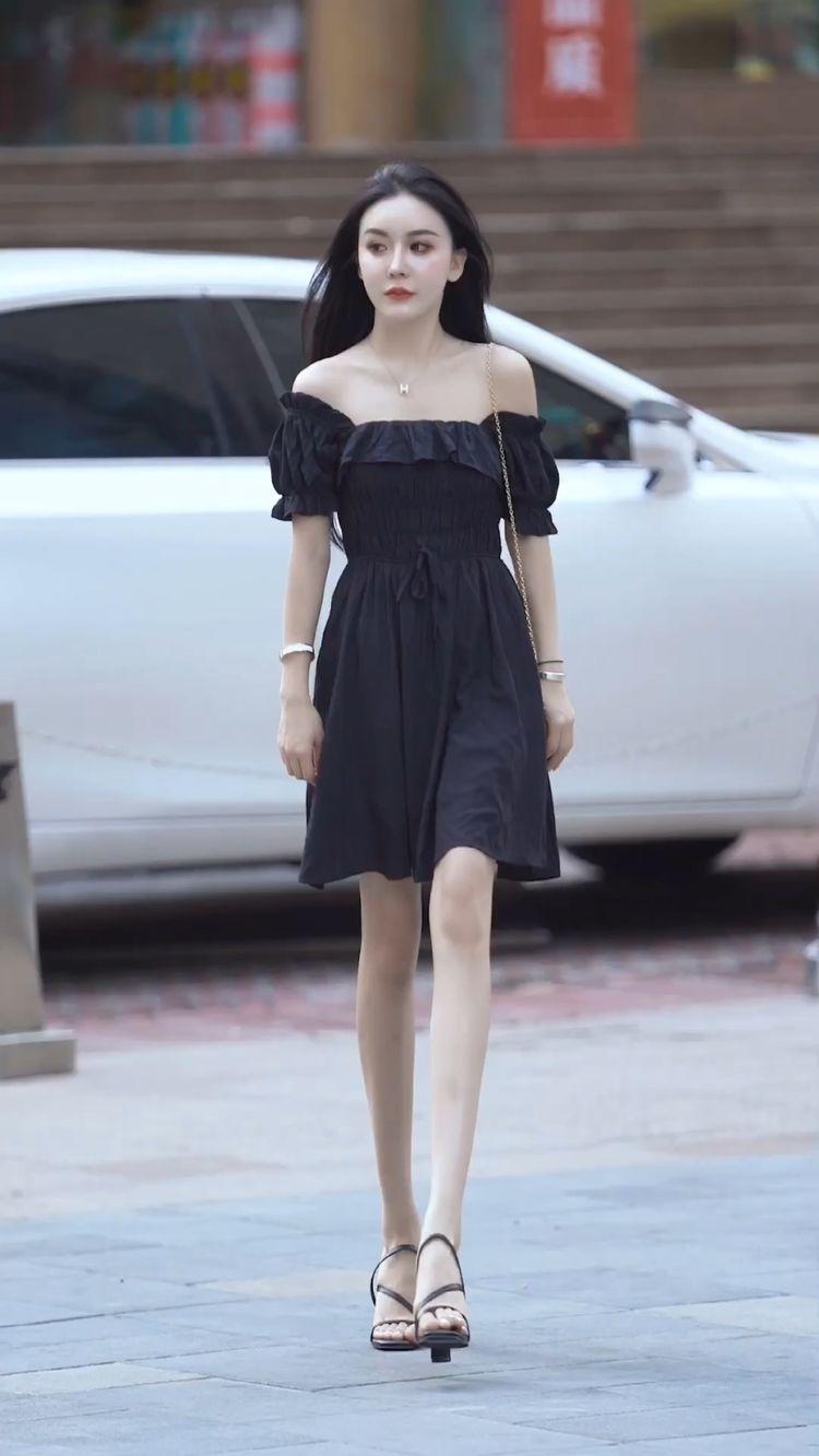 黑色一字肩连衣裙搭配黑色高跟鞋,贴合
