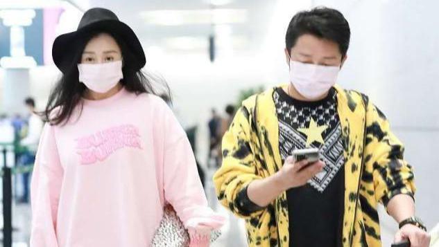 冉莹颖机场穿成孕妇,粉色卫衣配金色靴子够前卫,老公也爱粉口罩