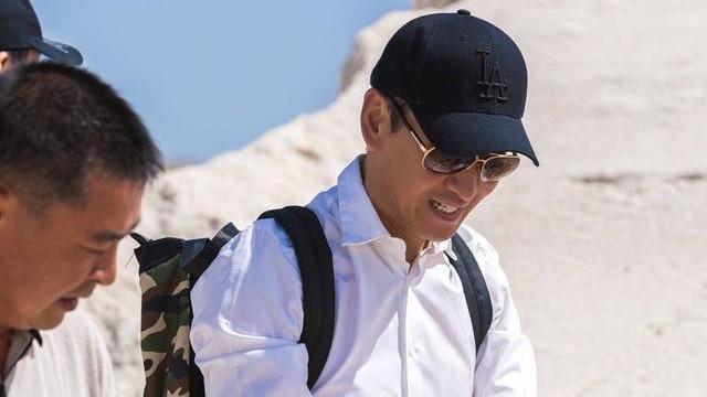 稻米地的时髦达人,周杰戴棒球帽配衬衣蹲田里,默默捐2万斤大米