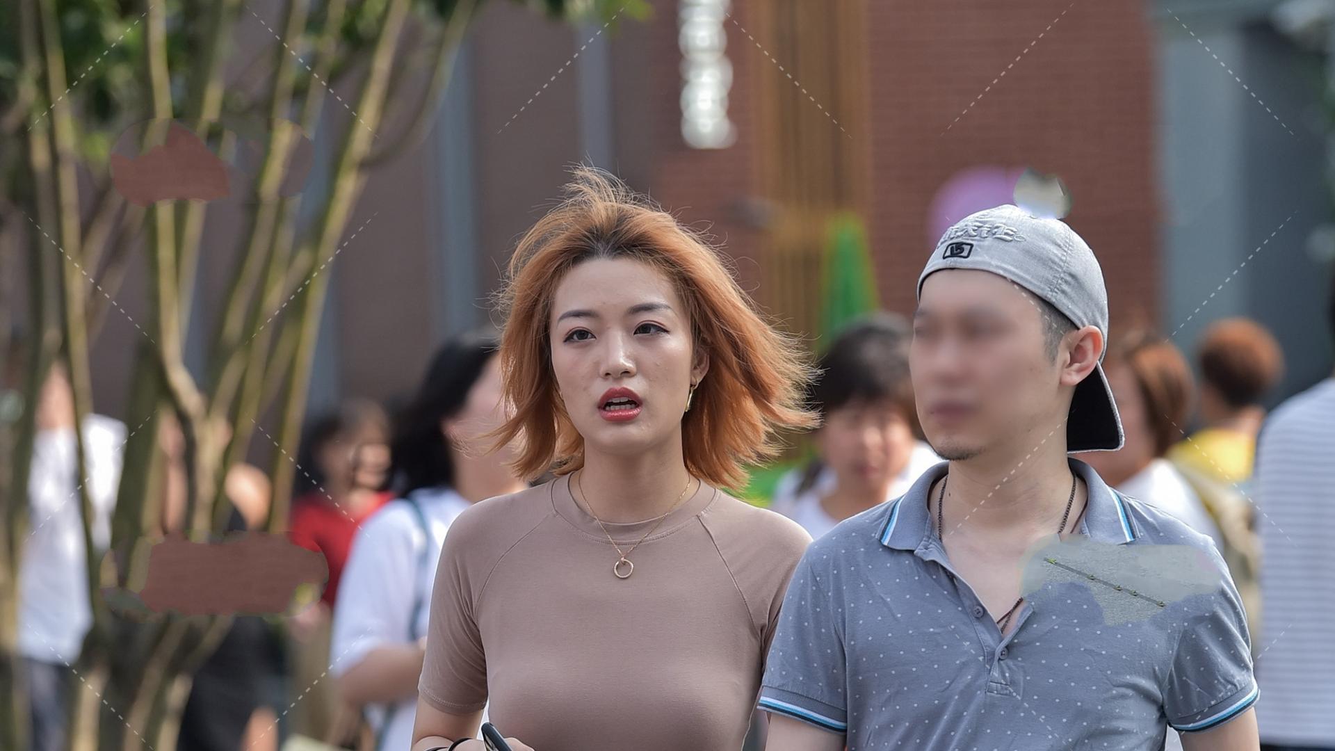 卡其色圆领短款短袖T恤搭配黑色手提包,体现出成熟女性的魅力